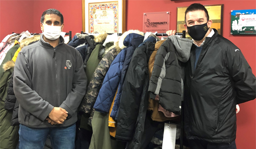 Image of 2 men stood by a rack of winter coats.