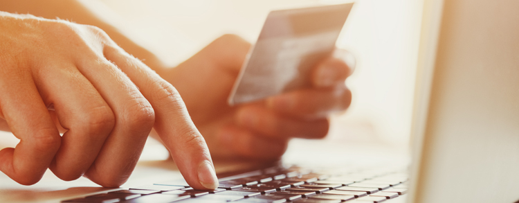 A picture of a person making an online payment using their laptop