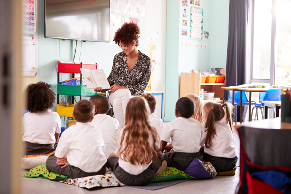 Picture of a teacher reading to primary school children