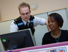 A photograph showing a police officer looking at information on a laptop with a colleague